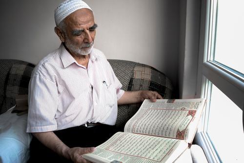 Weiser alter muslimischer Mann, der Taqiyah trägt, liest türkische Übersetzung des Koran in Leidenschaft weise Islam taqiyah Schädeldecke Fenster Sitzen