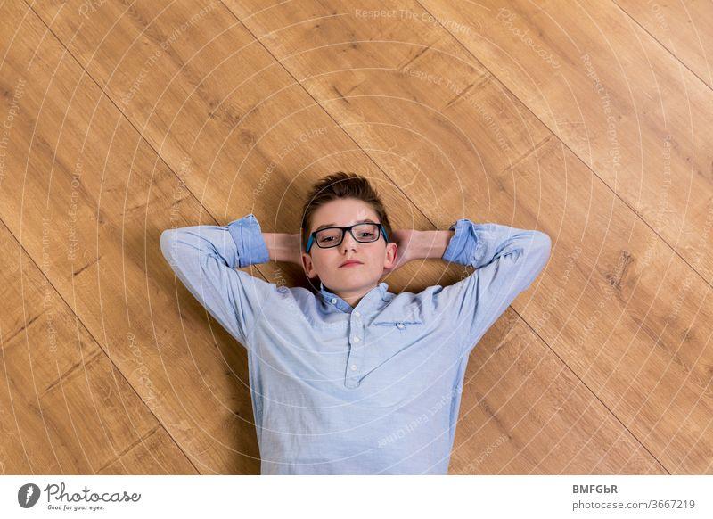 Teenager mit Brille liegt entspannt auf Holzboden zu Hause Junge liegen Boden Holzbolden Parkett Homeschooling Oberkörper Teenie jugendlicher zu Hause bleiben