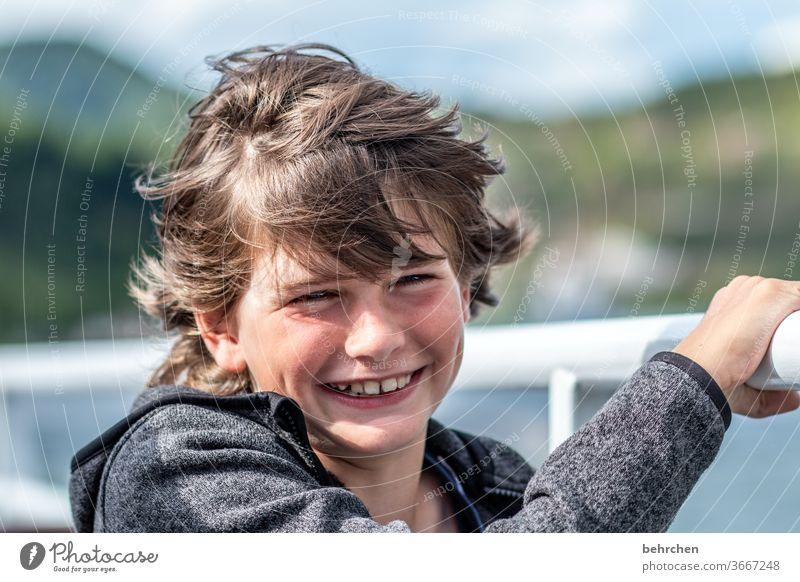 stürmische zeiten frech lange Haare Farbfoto Familie Nahaufnahme Kind Junge Kindheit Gesicht Tag Licht Kontrast Porträt Sonnenlicht Haare & Frisuren Mund Lippen