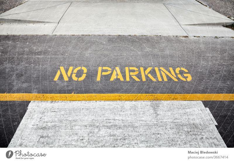 Gelbes Parkverbotsschild auf einer Straße. kein Parken Zeichen Symbol parken Verkehr Farbe Transport Asphalt gelb Ermahnung urban nein Linie Text Sicherheit