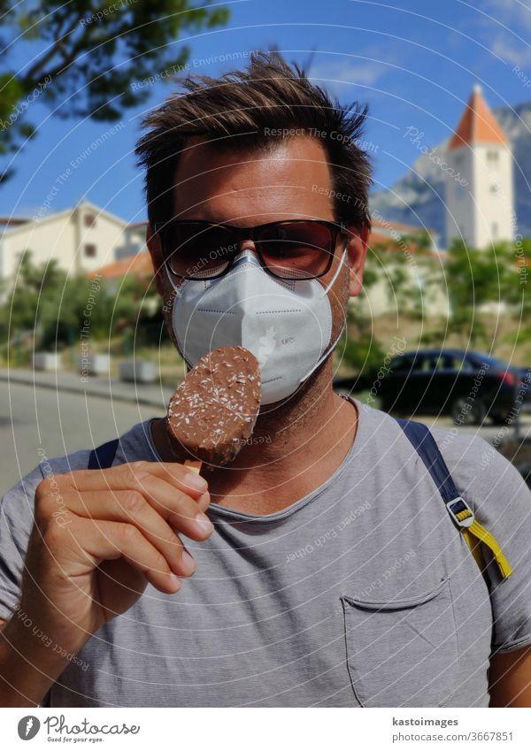 Junger Kerl in den Sommerferien, der eine Gesichtsmaske mit Coronavirus-Schutz trägt und nicht in der Lage ist, Eiscreme-Riegel zu lecken. Eiscreme-Bar