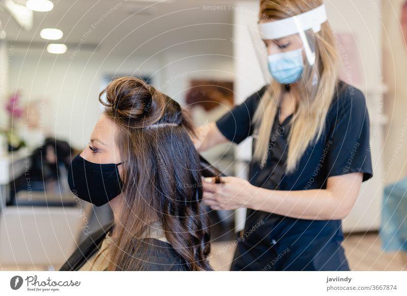 Friseurin, durch eine Maske geschützt, kämmt in einem Salon die Haare ihrer Kundin mit einem Bügeleisen. Frau bügeln Wellen Behaarung Mädchen Frisur Pflege