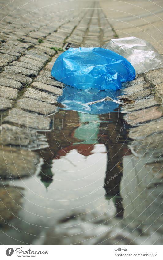 die welt versinkt in plastik Plastiktüte Plastikmüll Pfütze Umweltverschmutzung Rathaus Spiegelung Pflastersteine Kunststofftüte Plastetüte Kunststoffprodukt