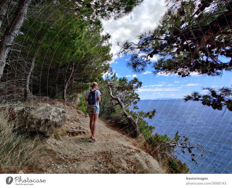 Junge Frau in den Sommerferien, die auf einem Küstenpfad durch Kiefernwald wandert, der kleine Buchten des adriatischen Mittelmeers verbindet. Mädchen Weg