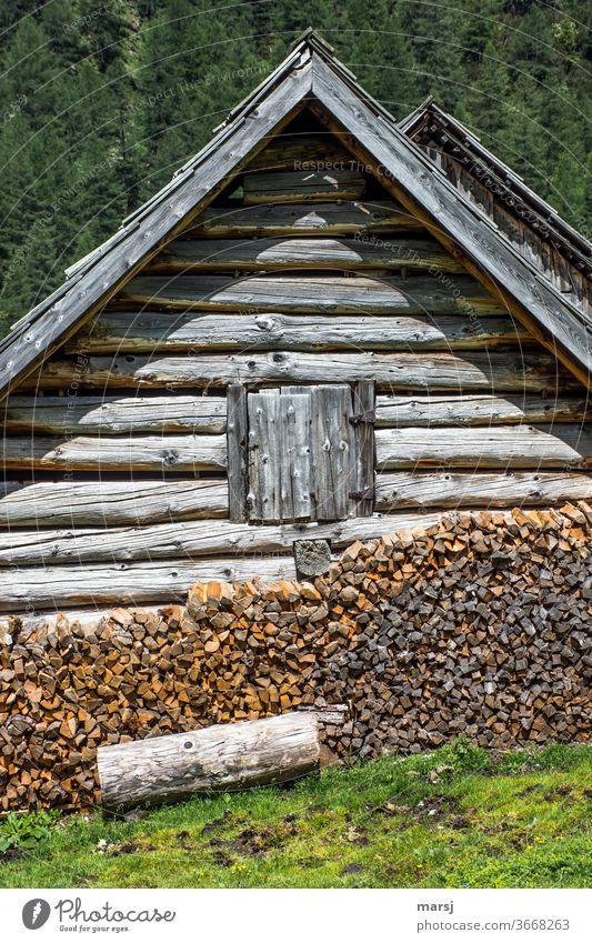 Genügend Holz vor der Hütte mit dem geschlossenen Fenster co2 CO2-neutral Brennholz geschlossenes Fenster gestapelt braun Holzstapel Brennstoff Stapel