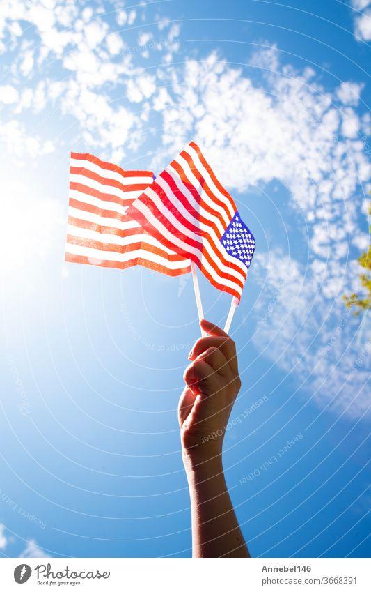 Hand hält zwei amerikanische Flaggen am blauen Himmel mit Sonnenhintergrund, winkende Fahne für die Vereinigten Staaten von Amerika in Nahaufnahme national