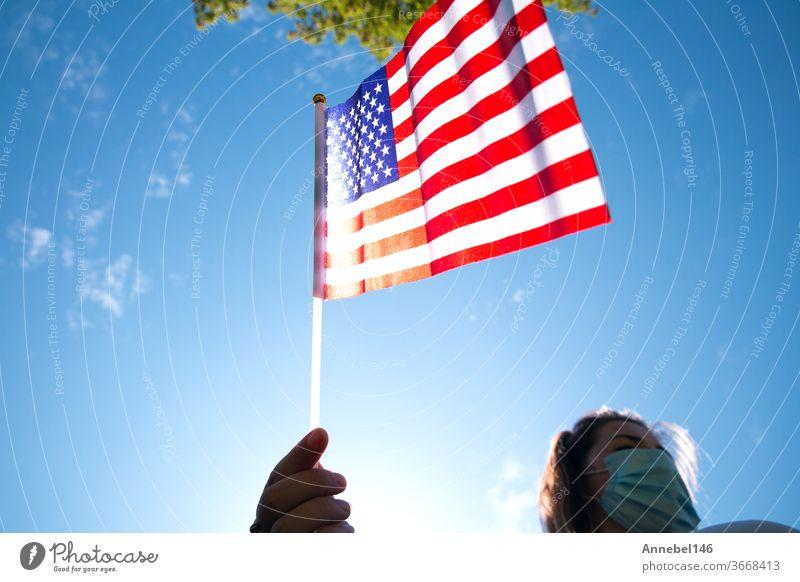 Junge Frau hält amerikanische Flagge am blauen Himmel mit Sonnenlicht und Sicherheitsmaske für Covid-19, der für Usa winkt USA Patriotismus Patriotin im Freien