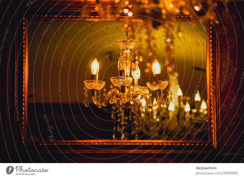 Die Party geht gleich los. Der Kerzenlüster ist schon an und im Spiegel mit goldenem Rahmen lässt sich einiges erahnen... Glas Reflexion & Spiegelung