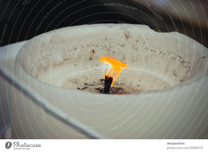 , Eine Kerze die flackert in einem weißen Behälter. (Zum Gedenken ) Kerze brennt Flamme Licht Brand Kerzendocht Wachs Kerzenschein brennen Weihnachten & Advent
