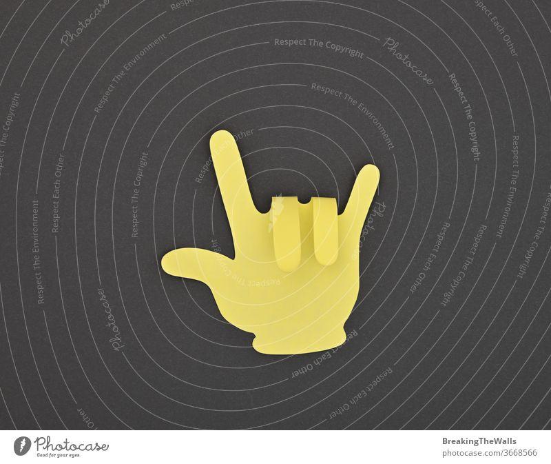 Papiergefertigter gelber HORNS-Gestenaufkleber auf grau Hörner Teufel Felsen Musik Metall hart schwer gut gestikulieren Hand Form Finger gemacht Aufkleber