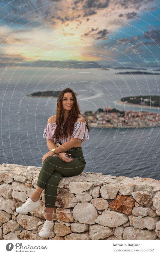Attraktive Brünette, die an einem warmen, sommerlich windigen Tag auf einer Steinmauer sitzt. Modisches Mädchen posiert mit dem adriatischen Meer und der kleinen Stadt Primosten im Hintergrund. Wunderschöner goldener Sonnenuntergang