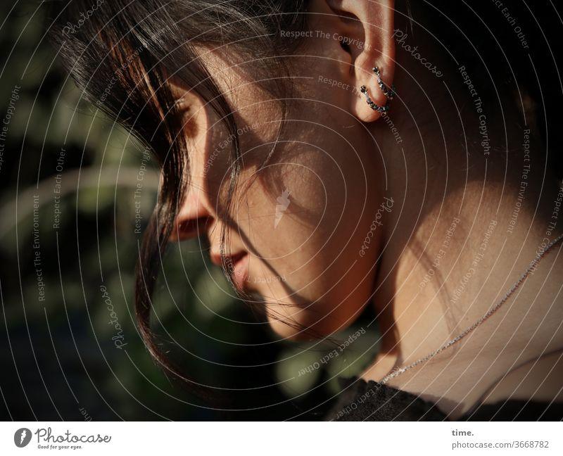 Estila profil sonnig abendlicht frisur haare gedankenverloren frau weiblich ohrringe schmuck vertieft stimmung melancholie konzentration schatten strähnchen