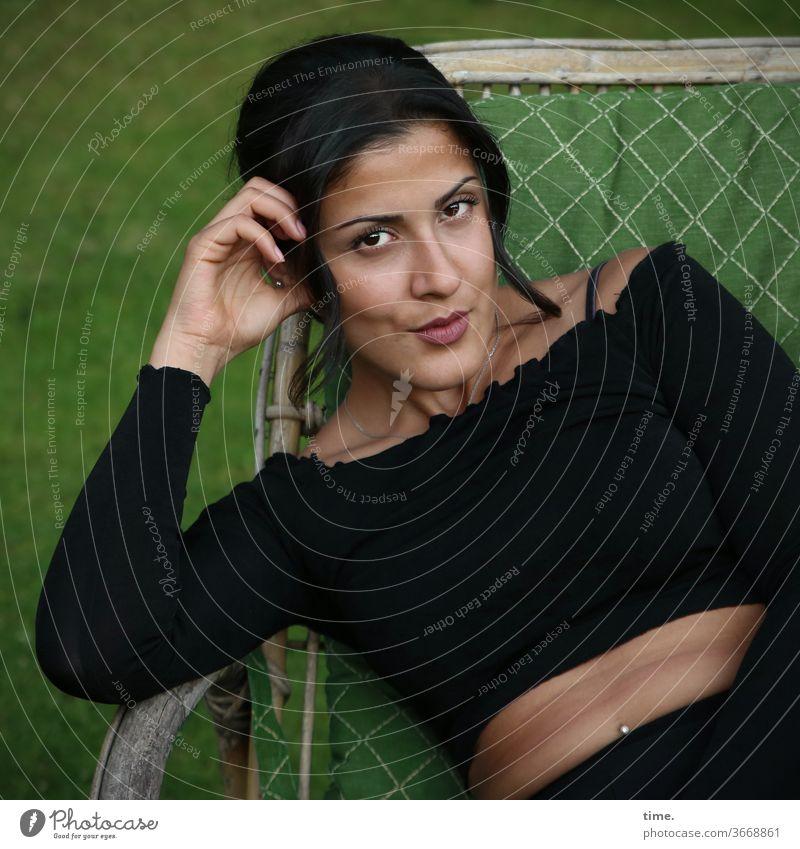 Estila | Lieblingsmensch frau feminin selbstbewusst sitzen garten stuhl blick aufstützen top piercing schwarzhaarig langhaarig ernsthaft skeptisch prüfend