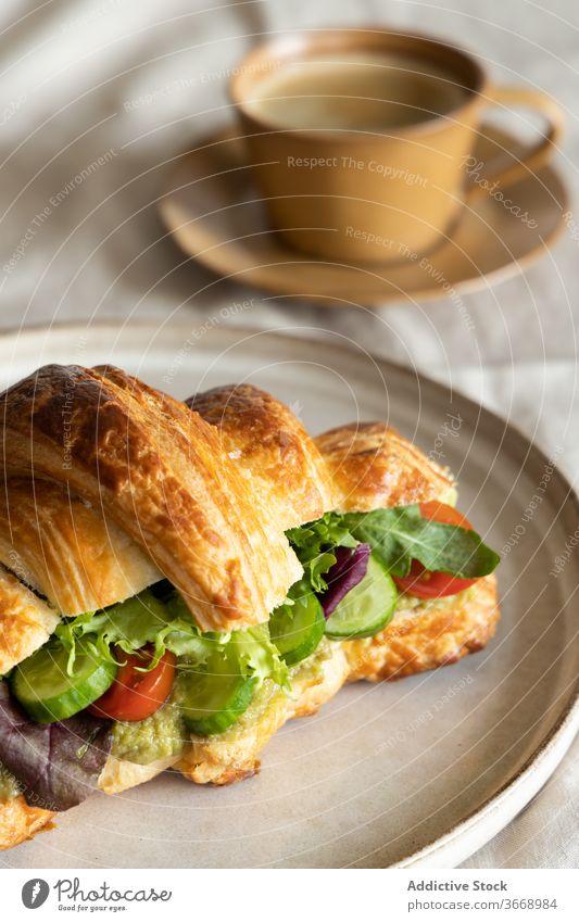 Köstliches veganes Sandwich auf Teller Veganer Frühstück Belegtes Brot Gemüse Morgen lecker frisch geschmackvoll Snack Vegetarier Salat Tisch Tasse Kaffee