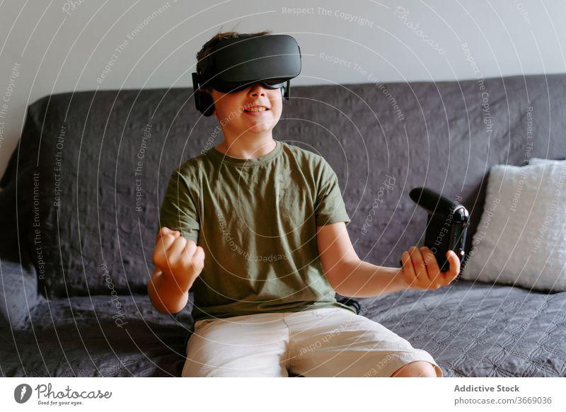 Kind in VR-Headset spielt auf der Couch Junge Schutzbrille spielen Gamepad virtuell Realität benutzend Sofa unterhalten modern heimwärts Gerät wenig bezaubernd