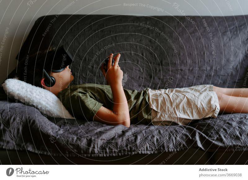 Kleiner Junge mit VR-Headset entspannt zu Hause auf der Couch Kind Sofa Schutzbrille Gamepad spielen Gerät unterhalten digital Innovation Apparatur modern wenig