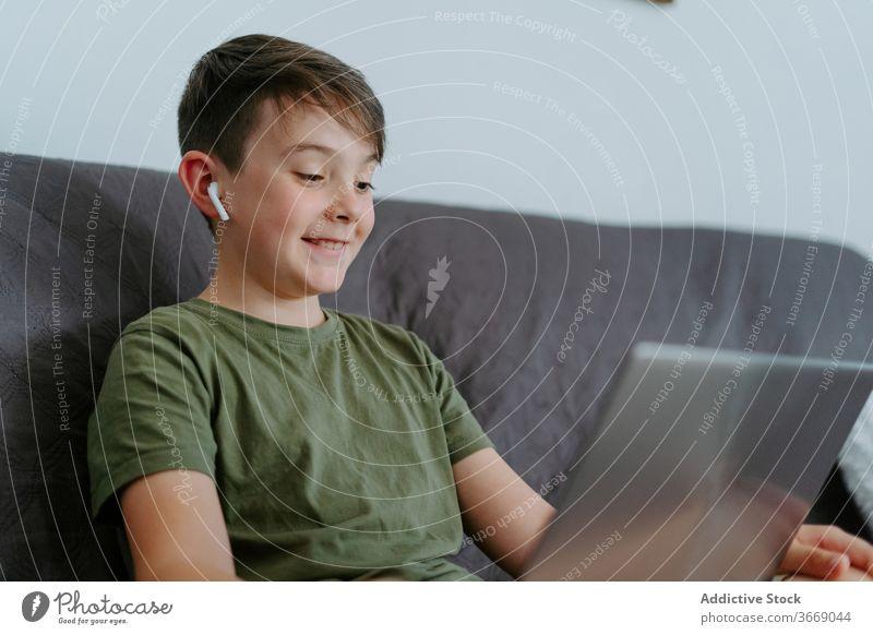 Bezauberndes Kind mit Videoanruf auf Laptop zu Hause Junge Video-Chat Kommunizieren Wellenhand Sofa heimwärts heiter Anruf Apparatur Glück Internet Gerät wenig
