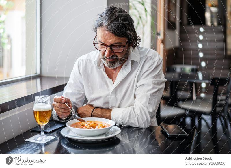 Bärtiger ethnischer Mann isst köstliches Mittagessen im Restaurant älter Café Glas Bier reif trinken positiv männlich ruhen Lächeln gealtert