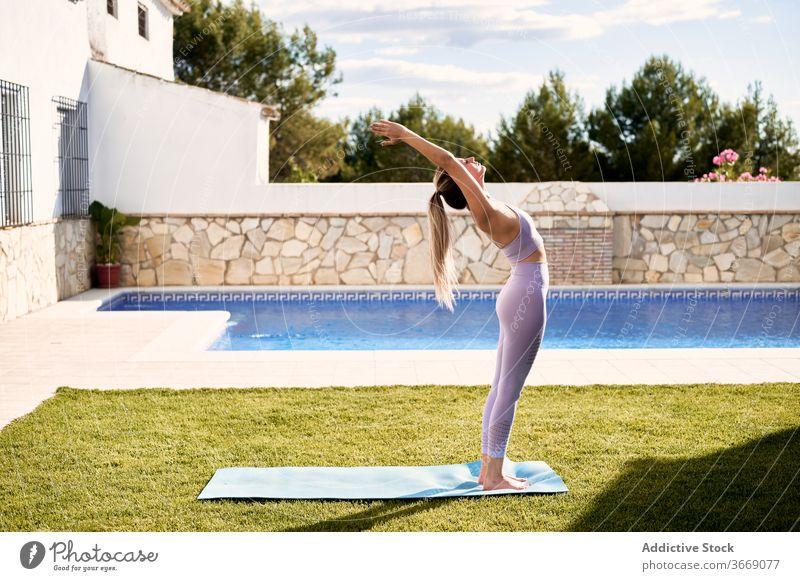 Ruhige Frau macht Yoga in Bergposition auf der Terrasse Berg-Pose urdhva hastasana üben Asana Sommer Unterlage Stressabbau schlank BH Leggings Pool Windstille