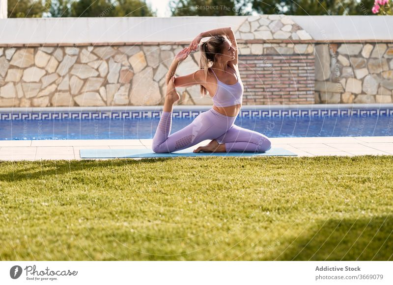Flexible Frau macht Yoga in King Pigeon Pose üben eka pada rajakapotasana Hof Unterlage ruhig beweglich Harmonie aktive Kleidung Asana Wellness sitzen schlank