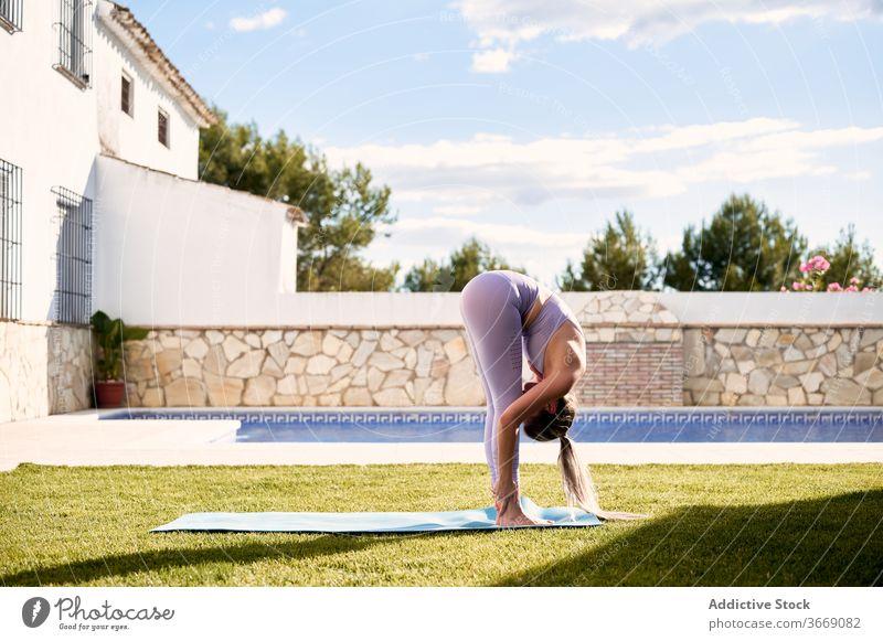 Frau macht Yoga in Uttanasana auf der Terrasse Vorwärtsbeuge üben uttanasana beweglich Asana Pose Rasen Sportbekleidung Wegbiegung Unterlage Gesundheit Übung
