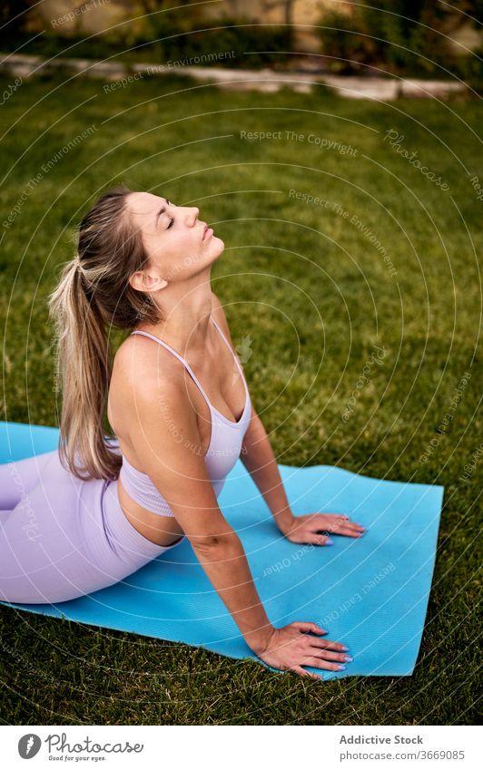 Ruhige Frau macht Yoga in Cobra-Pose Kobra-Pose üben bhujangasana Harmonie Hinterhof Rasen beweglich Asana friedlich Unterlage Augen geschlossen Übung