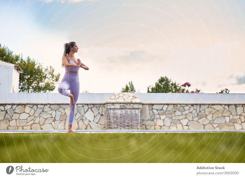 Ruhige Frau übt Yoga in Baum-Pose Baumhaltung Gleichgewicht vrksasana Namaste Windstille ruhig Unterlage Beckenrand Hinterhof Wasser Hof gestikulieren BH