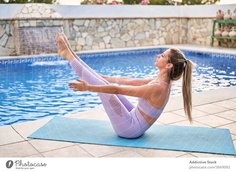 Frau in Bootspose auf Yogamatte Boot-Pose üben Gleichgewicht aktive Kleidung Beckenrand Sommer beweglich Konzentration Wellness Körper Asana Hof