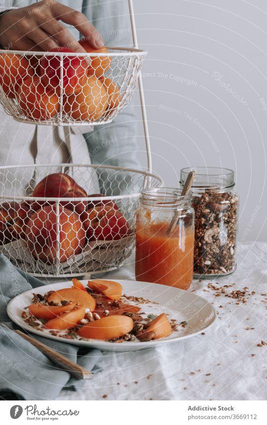 Crop-Person am Tisch während des Frühstücks Gesundheit Müsli Morgen Schalen & Schüsseln Frucht organisch Joghurt Lebensmittel frisch natürlich Vitamin lecker