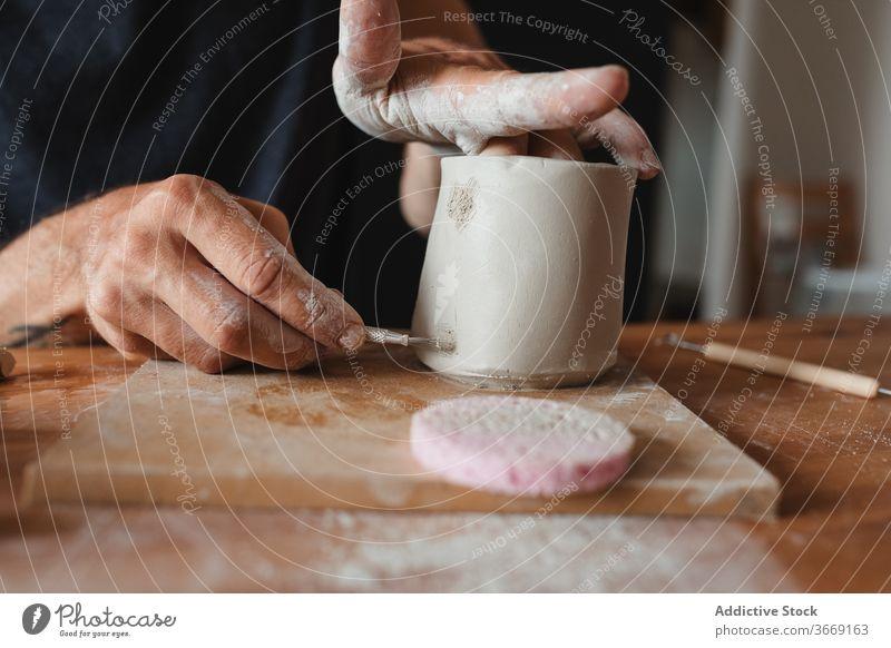 Crop männlich Keramiker schaffen Tasse Ton Kunstgewerbler Mann kreieren Herstellerin Fähigkeit Bürste Kunsthandwerker Werkstatt Handwerk professionell Hobby