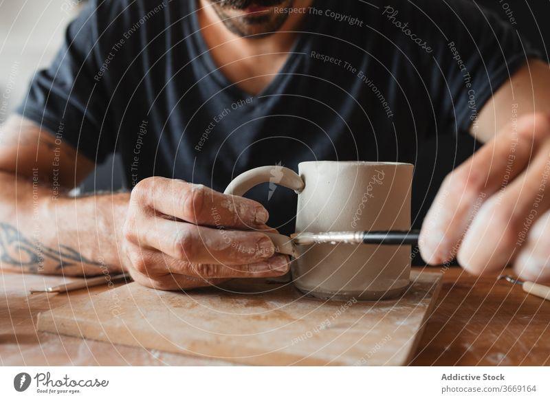 Crop männlich Keramiker schaffen Tasse Ton Kunstgewerbler Mann kreieren Herstellerin Fähigkeit Kunsthandwerker Werkstatt Handwerk professionell Hobby kreativ