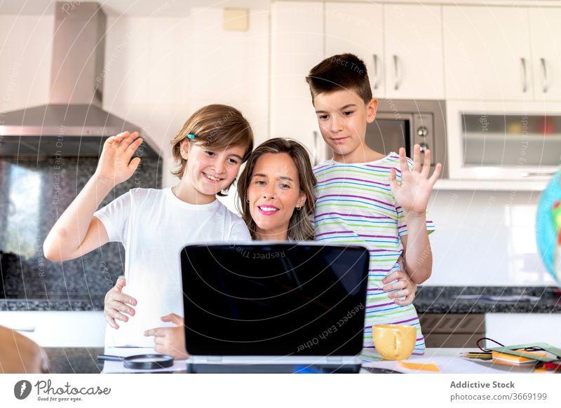 Mutter mit Söhnen, die während eines Videogesprächs auf dem Laptop grüßen Sohn Hallo Videoanruf Gruß Umarmen Kommunizieren Kindheit benutzend Gerät Apparatur