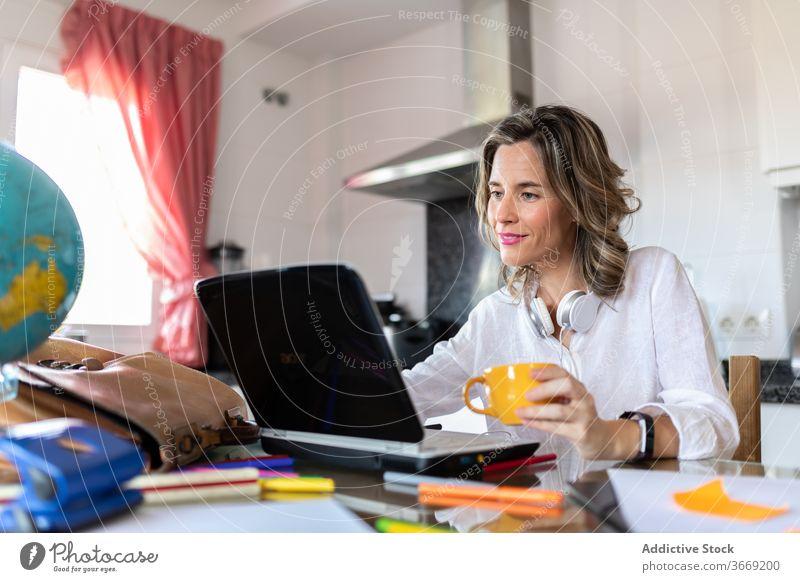 Positive Frau in Headset mit Videoanruf auf Laptop drinnen Tasse Heißgetränk Freizeit sprechen Lächeln benutzend Apparatur Gerät Netbook Gespräch Video-Chat