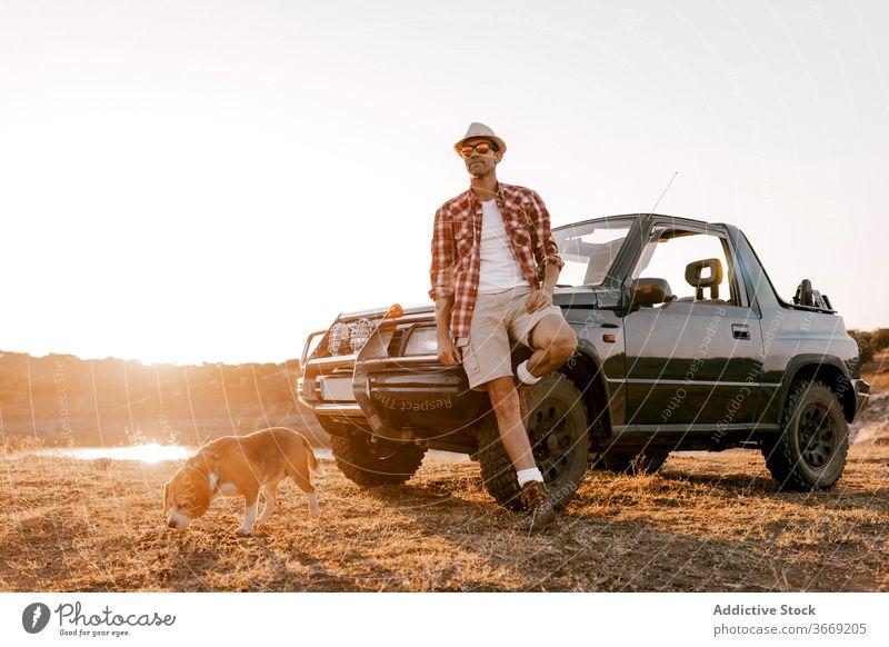 Tourist mit Rucksack stehen in der Nähe von Hund und Auto bewundern Natur nachdenken Hochland reisen Automobil Fluss Berge u. Gebirge idyllisch Harmonie