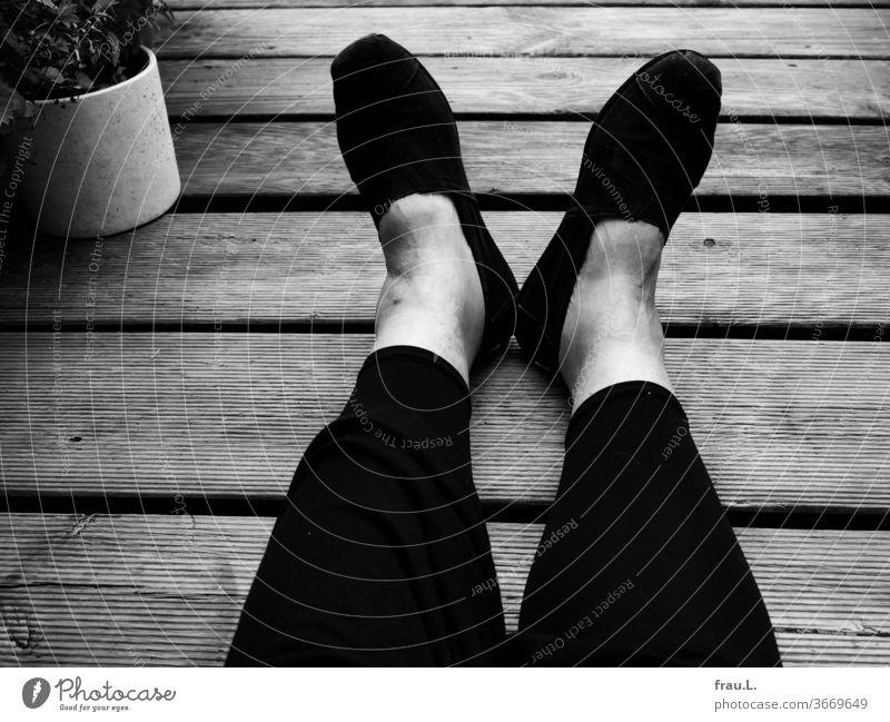 Schuhe, Füße, Leggings, Beine und ein Kleid liegen platt auf den Holzgrätlingen einer Dachterrasse. Der Rest der Frau ist nicht zu sehen. sitzen Balkon Erholung