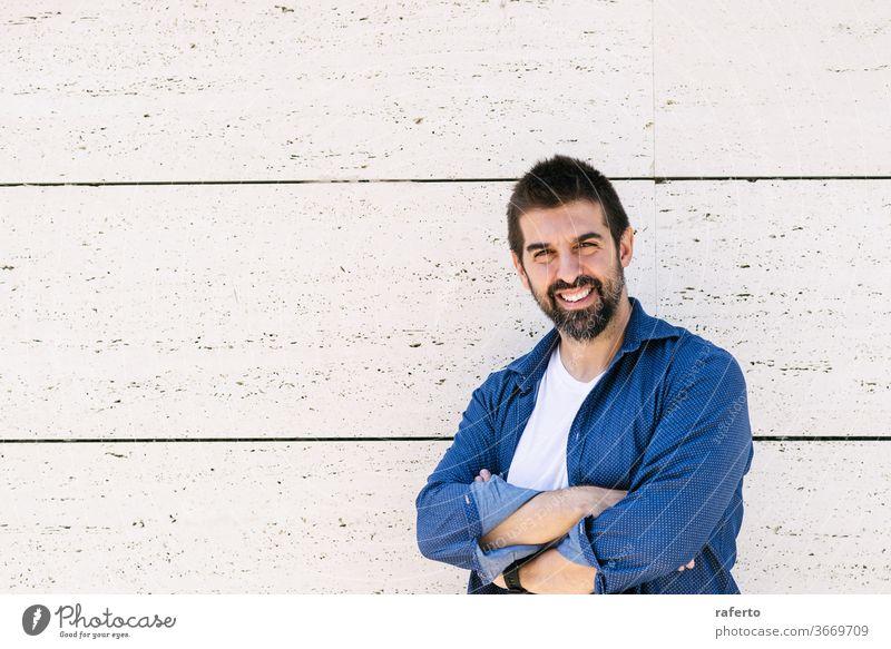 Bärtiger Mann lehnt mit verschränkten Armen an der Wand und schaut lächelnd in die Kamera 1 männlich Stehen bärtig heiter attraktiv hispanisch Lehnen