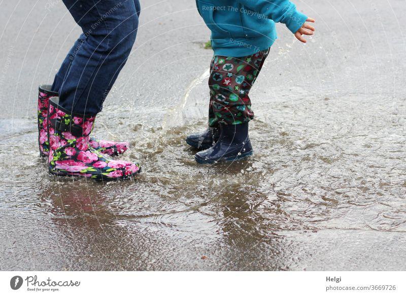 Pfützenspaß - Mutter und Kind haben Spaß beim Sprung in die Pfütze Detailaufnahme Beine Gummistiefel springen platsch Freude platschen spritzen Wasser nass