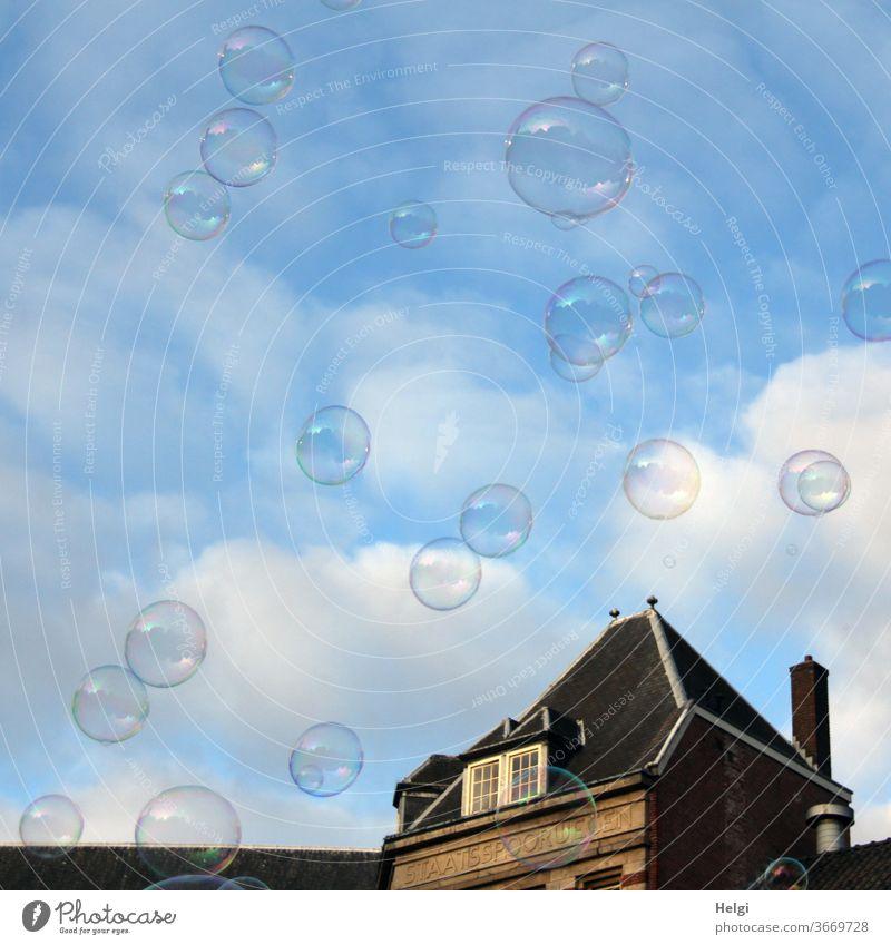 viele Seifenblasen vor blauem Himmel mit Wolken, im Hintergrund ein Gebäude Architektur Haus Leichtigkeit fliegen Amsterdam Außenaufnahme Stadt