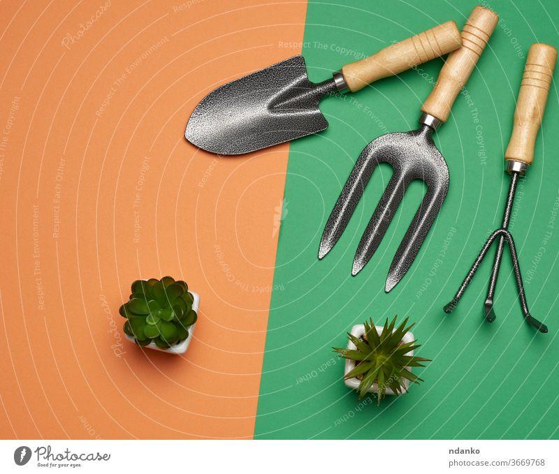 Gartenset mit Schaufeln, Harken, Heugabeln auf grün-orangem Hintergrund, Draufsicht Ackerbau Bett schwarz Botanik braun Sauberkeit Ausschnitt Nahaufnahme