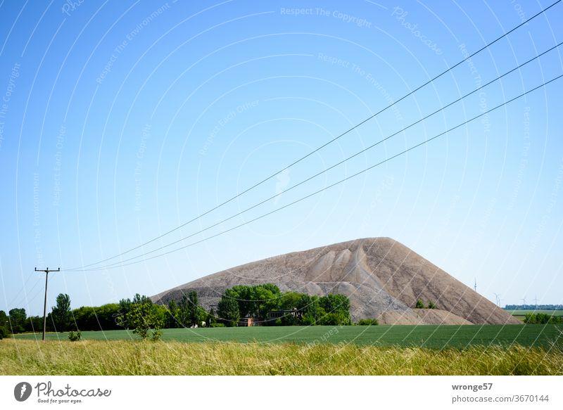 Mansfelder Revier | Landschaft mit Abraumhalde und einer diagonal durch den Bildvordergrund verlaufenden Freileitung Mansfelder Land Bergbau Kupferbergbau