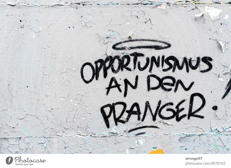 Opportunismus an den Pranger steht mit schwarzer Farbe an eine grauen Wand schwarze Farbe graue Wand alt abblätternd sprayen sprühen Graffitto Graffiti Mauer