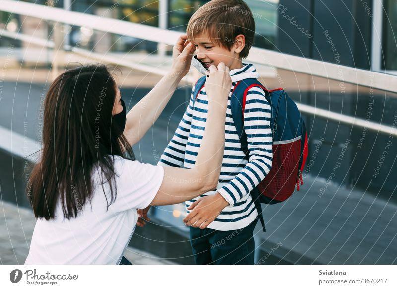 Die Mutter passt die Maske ihres Sohnes an. Eine Mutter und ihr Kind auf dem Weg zur Schule oder zum Kindergarten während einer Coronavirus-Pandemie. Schutzmaske als Krankheitsprävention, soziale Distanz
