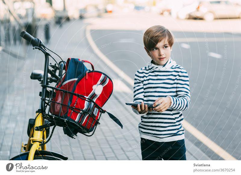 Ein süßer Junge in einem gestreiften Pullover hält eine Tafel in der Hand und steht neben einem Fahrrad, an dem ein Rucksack hängt. Der Junge wird nach der Schule auf einem Fahrrad nach Hause fahren. Sicherer Heimweg
