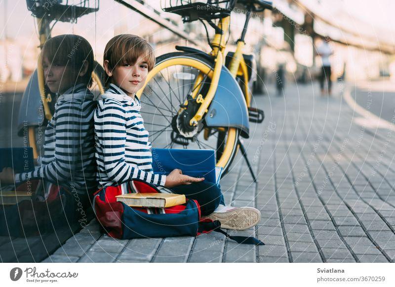 Ein niedlicher Schuljunge sitzt in der Schule unter freiem Himmel und hält ein Buch in den Händen. Daneben ein Schulrucksack und ein Fahrrad, Platz für Text