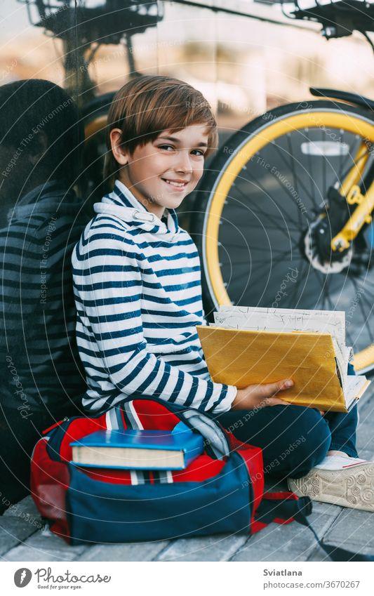 Ein fröhlicher Junge sitzt auf dem Bürgersteig in der Nähe der Schule und liest ein Buch. Daneben steht ein Fahrrad und ein Rucksack. Gesicht müde Deckung