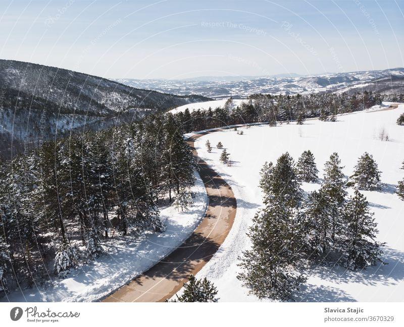 Winterlandschaft im Sonnenlicht. Blick auf die von immergrünen Bäumen umgebene Bergstraße im Winter, Drohnenschuss oben Antenne Asphalt Hintergrund Kabine kalt