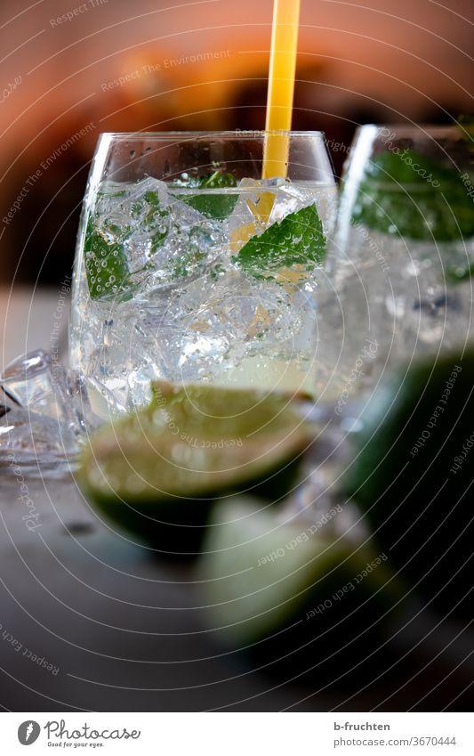 Trinkglas mit Eiswürfeln, Minze und Sodawasser. Limetten im Vordergrund Cocktail Getränk Lemon Soda Wasser Glas frisch trinken kalt Erfrischung Sommer Zitrone