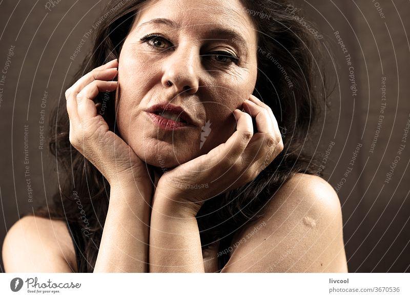 Porträt einer reifen Frau mit Händen nahe am Gesicht schön attraktiv Reife Frau Menschen romantisch romantische Haltung Hand Hände in Gesichtsnähe braun