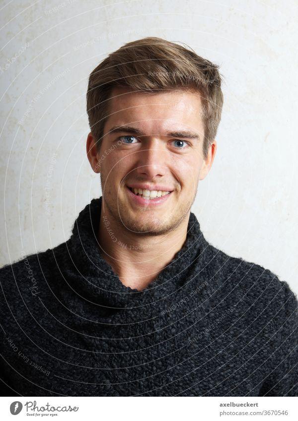 junger Mann lächelt Lächeln blond Dreitagebart Rollkragenpullover gutaussehend unrasiert Bartstoppel männlich Porträt Kaukasier attraktiv Erwachsener Lifestyle