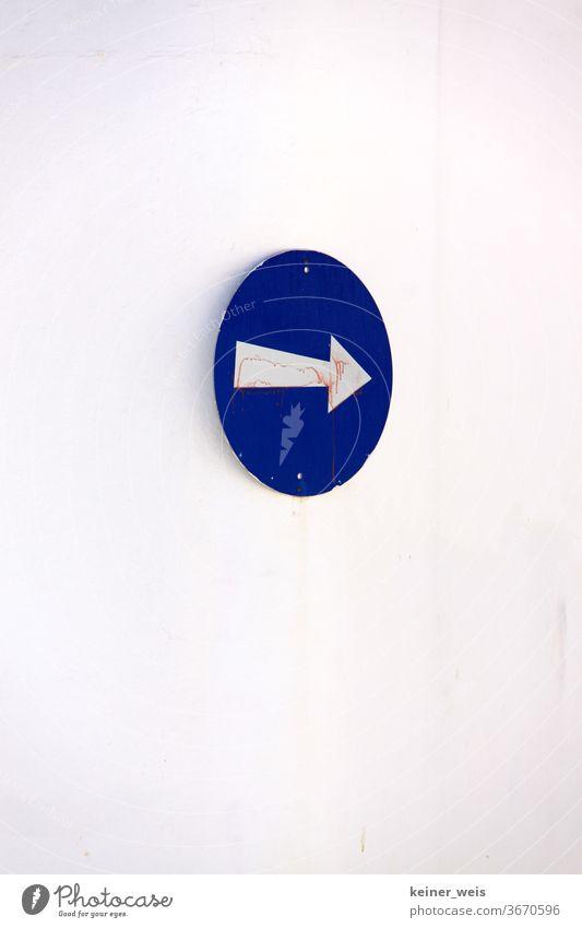 Blaues Schild mit weißem Pfeil blau Wand rund rechts Richtung Weg Einbahnstraße Griechenland Südeuropa hochformat Verkehr Straßenverkehr Verkehrsschild Symbol